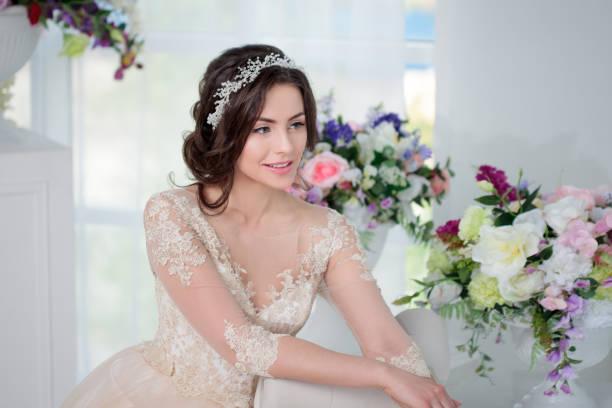 porträt von schönen mädchen in ein luxuriöses brautkleid. braut mit schöner dekoration im haar, lächeln - verlobungskleider stock-fotos und bilder