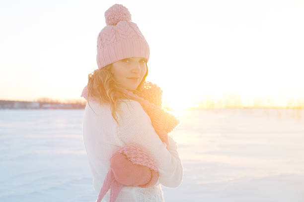 Portrait of beautiful girl in pink hat on winter field stock photo
