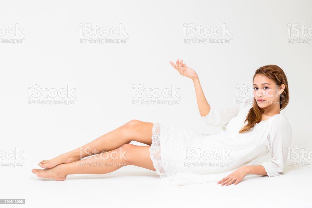 portrait of beautiful girl lying on the white floor stock photo