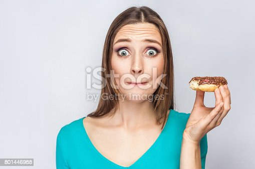 692840848istockphoto Portrait of beautiful girl with chocolate donuts. 801446988
