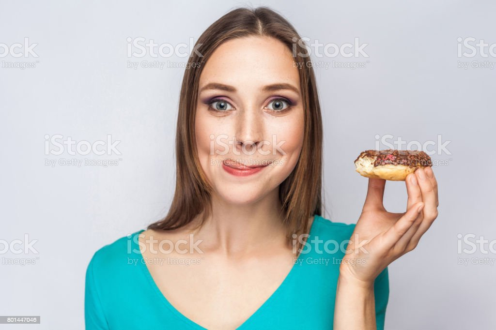Portrait of beautiful girl with chocolate donuts.