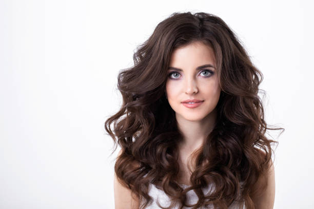 Portrait of beautiful girl with luxuriant hair curling. stock photo