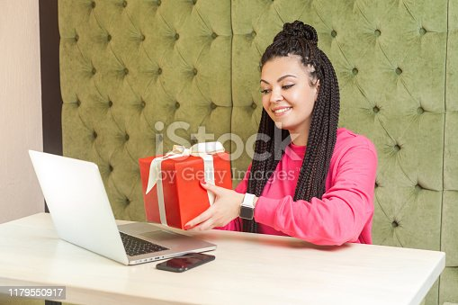 Portrait of beautiful happy young woman with black dreadlocks in pink blouse sitting in cafe, holding red present box, showing her friend gift throught webcamera at laptop, toothy smile. Indoor