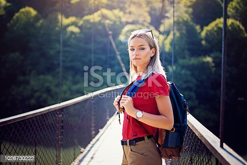 Portrait of beautiful hiker girl standing on the rope bridge over river in the forest