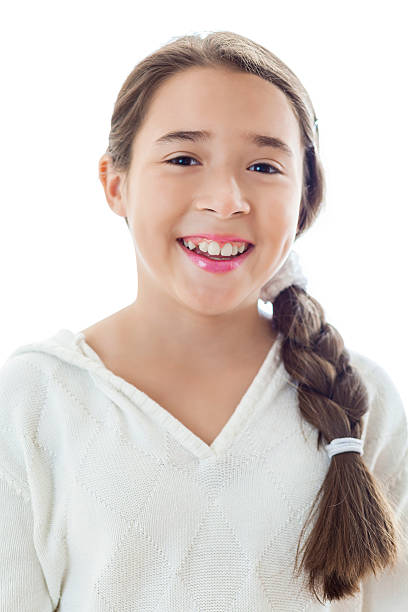 Portrait of beautiful Hispanic preteen girl Beautiful Hispanic preteen girl smiles confidently while looking at the camera. Her long brown hair is in a braid that falls over her shoulder to the side. She is wearing a white sweater. She has brown eyes. cute middle school girls stock pictures, royalty-free photos & images