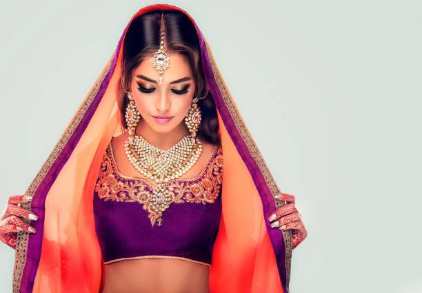 porträt von schöne indische mädchen in eine traditionelle nationale anzug gekleidet und mehndi tattoo auf ihren händen bemalt. - indische kultur stock-fotos und bilder