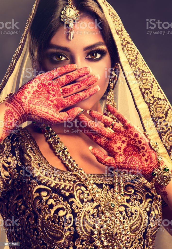 e58ef4f7b1 Portrait of beautiful indian girl dressed in a traditional national suit  with mehndi tattoo is painted