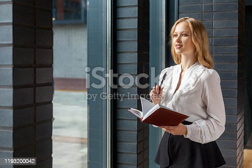 1176252245 istock photo Portrait of beautiful inspired young woman making notes in diary book, looking out window while pondering idea. indoors 1193200042