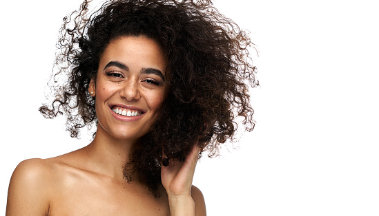 Portrait of beautiful cheerful latin american woman with afro hairstyle looking at camera, isolated on white background