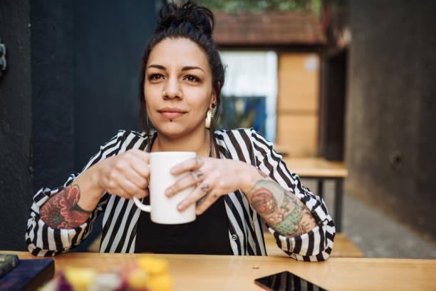 porträt der schönen latina /mexican tausendjährigen frau mit tätowierungen kaffeetrinken - kaffeetasse tattoo stock-fotos und bilder