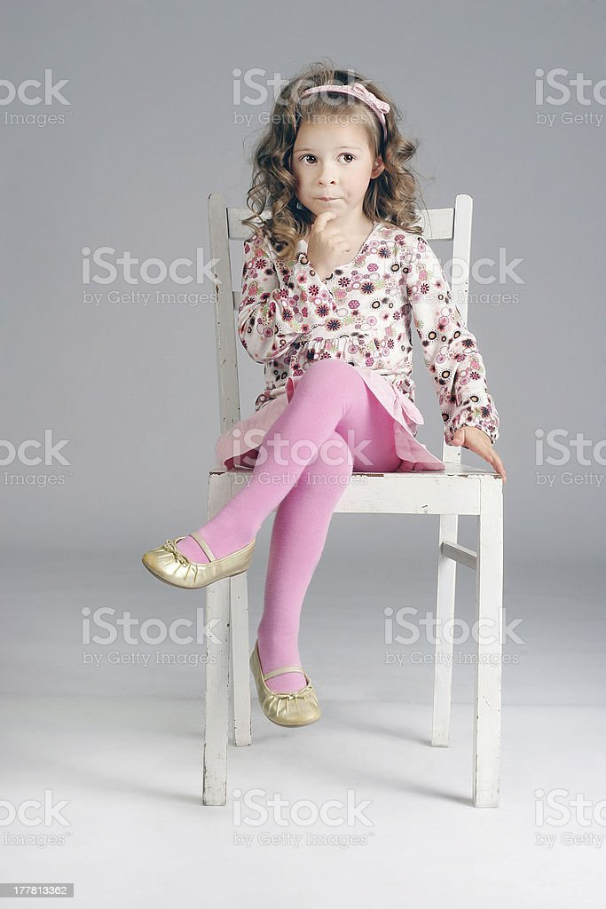 Portrait of beautiful little thoughtful girl on the white chair. royalty-free stock photo