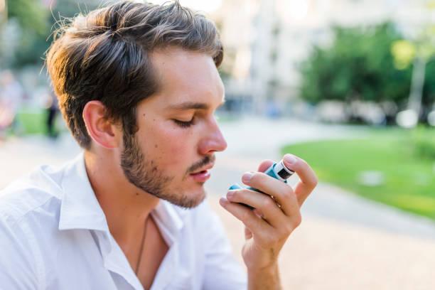 portrait d'un homme beau à l'aide d'inhalateur asthme dans le parc - technique photographique photos et images de collection