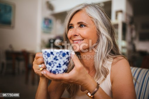Beautiful senior woman with gray hair enjoying a cup of coffee during breakfast at cafe