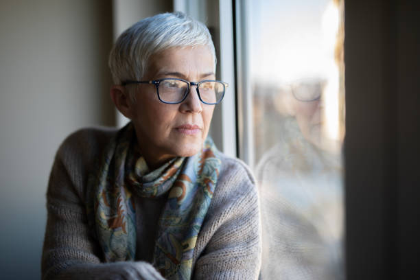 Portrait of beautiful mature woman relaxing by the window stock photo