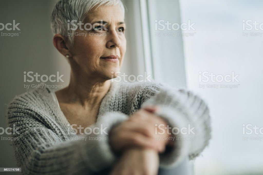 Portrait of beautiful mature woman relaxing by the window. stock photo