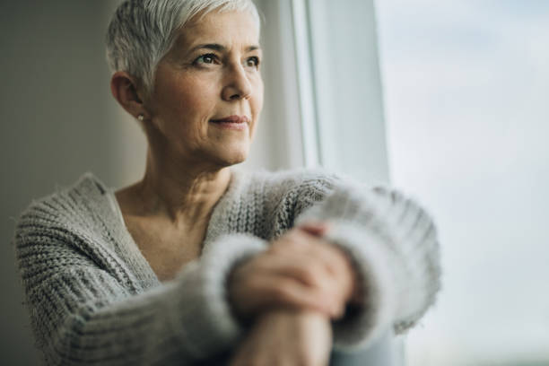 portrait of beautiful mature woman relaxing by the window. - looking at view stock pictures, royalty-free photos & images