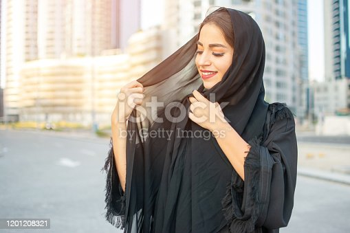 Portrait of beautiful middle eastern woman wearing abaya on the street