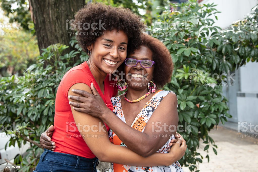Portrait of beautiful mother and daughter embracing each other while looking at camera with a toothy smile Portrait of beautiful mother and daughter embracing each other while looking at camera with a toothy smile very happy Mother Stock Photo