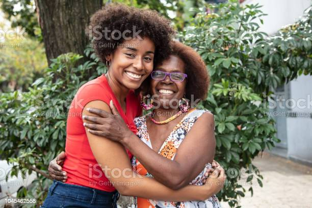 Portrait Of Beautiful Mother And Daughter Embracing Each Other While Looking At Camera With A Toothy Smile Stock Photo - Download Image Now