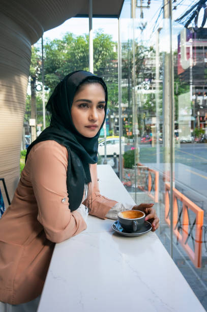 Retrato de hermosa mujeres musulmanas tener una taza de café. - foto de stock