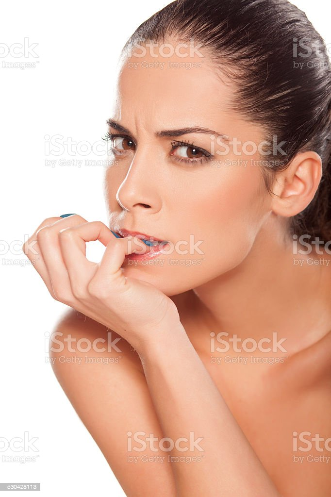 Portrait of beautiful nervous girl biting her nails stock photo