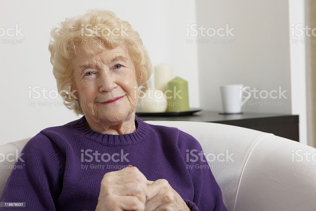 Portrait of beautiful old woman sitting on sofa at home royalty-free stock photo