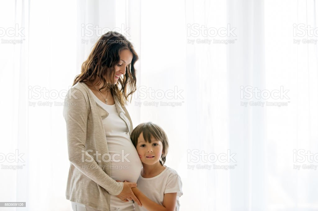 Portrait of beautiful pregnant woman and her cute child stock photo