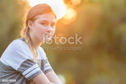 Portrait of pretty Caucasian preteen girl with the sun setting in the background. Copy space available.