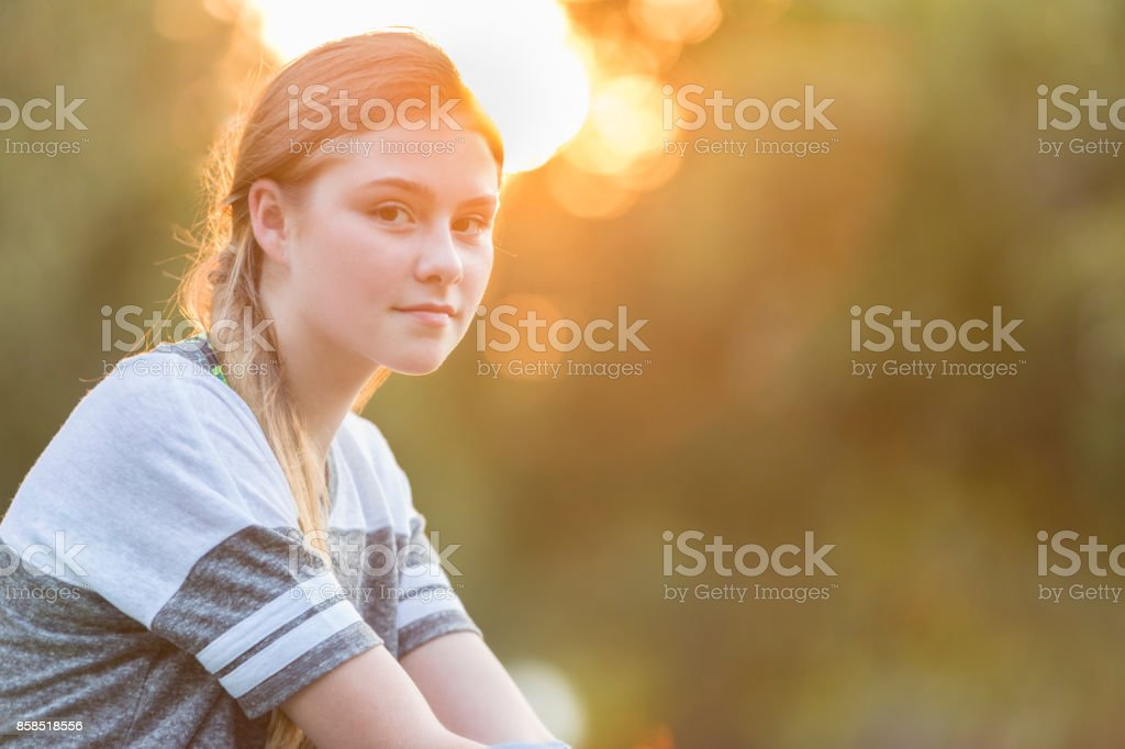 Portrait of beautiful preteen girl at sunset stock photo