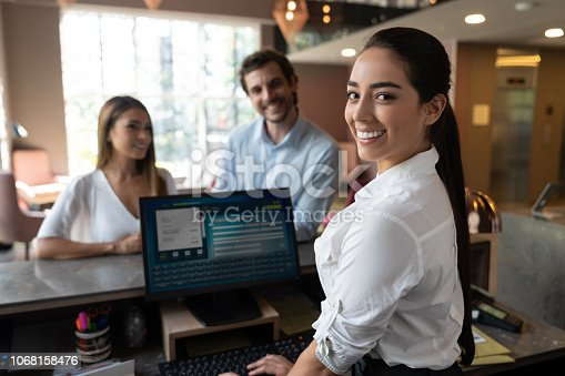 istock Portrait of beautiful receptionist at hotel doing check in for business couple 1068158476