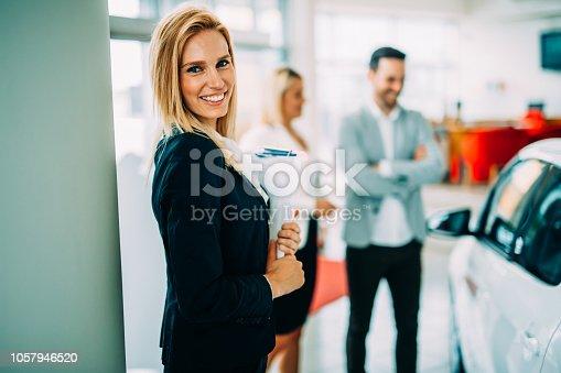 istock Portrait of beautiful saleswoman standing inside vehicle showroom 1057946520