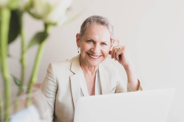 Portrait of beautiful senior professional woman at desk stock photo