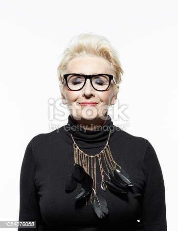 Glamour portrait of beautiful confident senior woman, wearing black clothes, glasses and jewelry, smiling at camera with eyes closed.