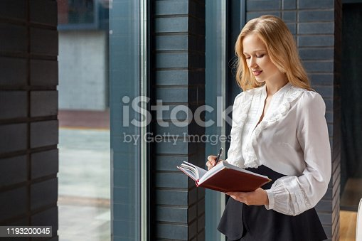 1176252245 istock photo Portrait of beautiful sensual businesswoman making notes in diary book. standing near window indoors 1193200045
