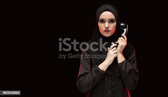 istock Portrait of beautiful serious scared young muslim woman wearing black hijab holding telephone to call as choice concept on black background 963938860