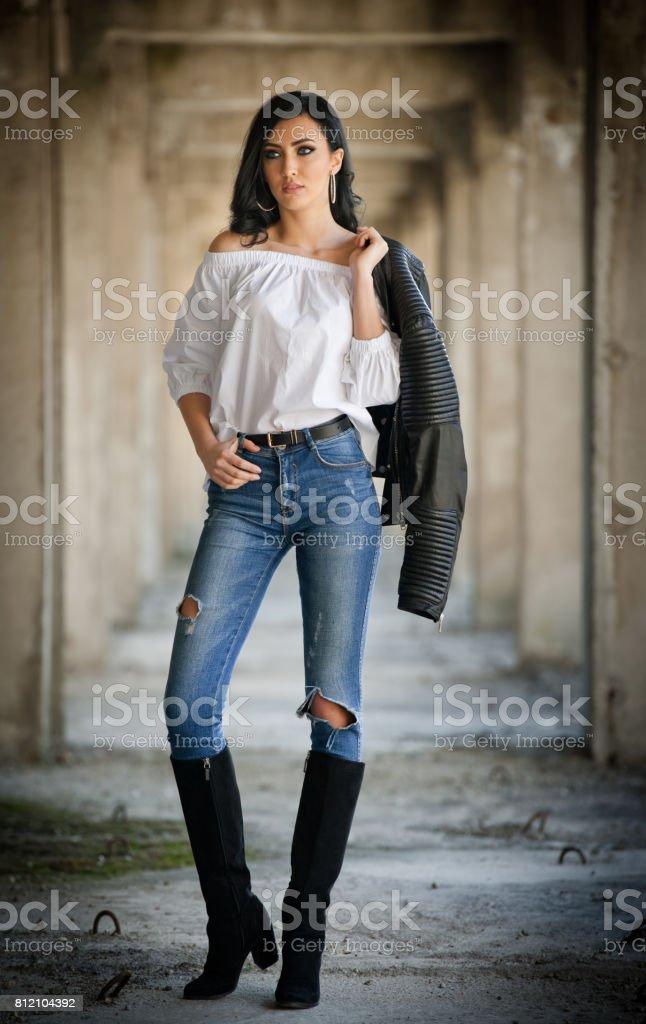 Porträt von schönen sexy junge Frau mit modernen Outfit, Lederjacke, Jeans, weiße Bluse und schwarze Stiefel im städtischen Hintergrund. Attraktive junge Brünette mit lange Haare und blaue Augen posieren. – Foto