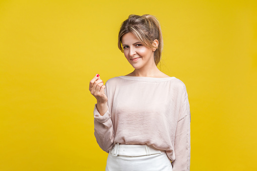 Portrait of beautiful smart young woman with fair hair in casual blouse standing, showing money gesture and looking at camera, asking financial reward. indoor studio shot isolated on yellow background