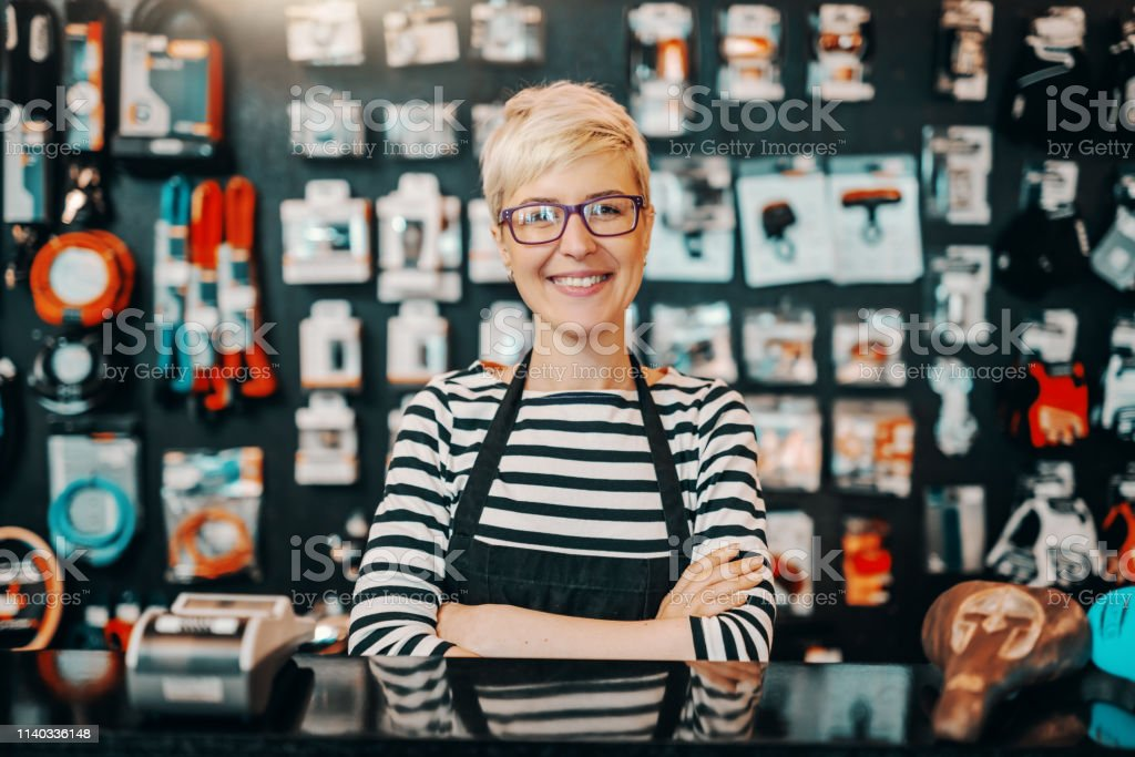Portrait of beautiful smiling Caucasian female worker with short blonde hair standing in bicycle shop with arms crossed. Portrait of beautiful smiling Caucasian female worker with short blonde hair standing in bicycle shop with arms crossed. Adult Stock Photo