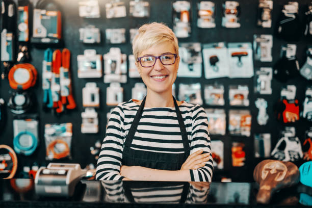 portrait of beautiful smiling caucasian female worker with short blonde hair standing in bicycle shop with arms crossed. - vendere foto e immagini stock