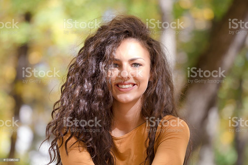 Portrait of beautiful smiling curly girl outdoor in autumn forest. stock photo