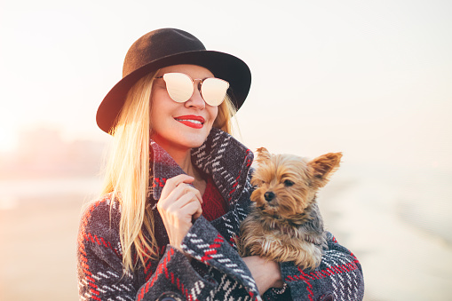 Portrait of beautiful smiling hipster trendy blonde woman walking on the beach with a little dog wearing sunglasses and black hat