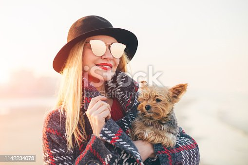istock Portrait of beautiful smiling hipster trendy blonde woman walking on the beach with a little dog wearing sunglasses and black hat 1142234078