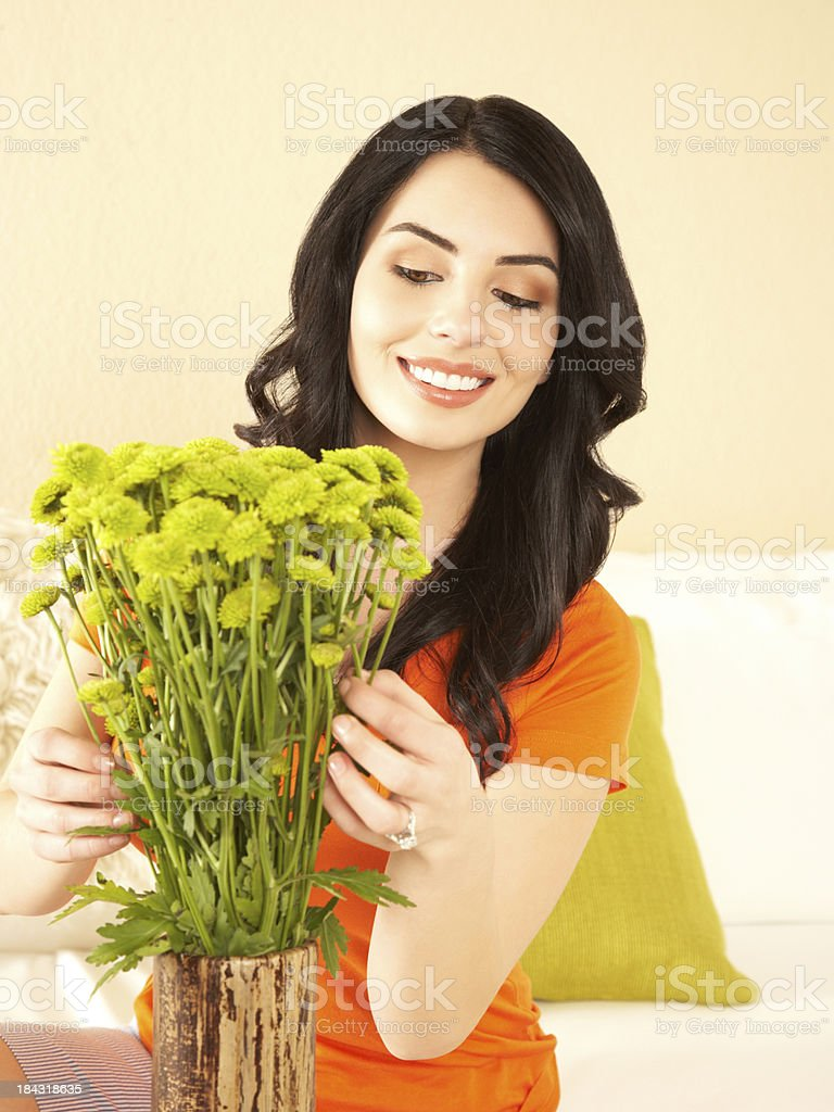 Portrait of beautiful smiling woman arranging flowers in a vase royalty-free stock photo
