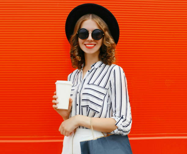 Portrait of beautiful smiling woman with coffee cup and shopping bags wearing white striped shirt, black round hat over red background stock photo
