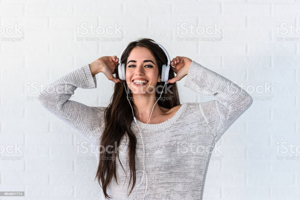 Portrait of beautiful smiling young woman with headphones indoors listening music royalty-free stock photo