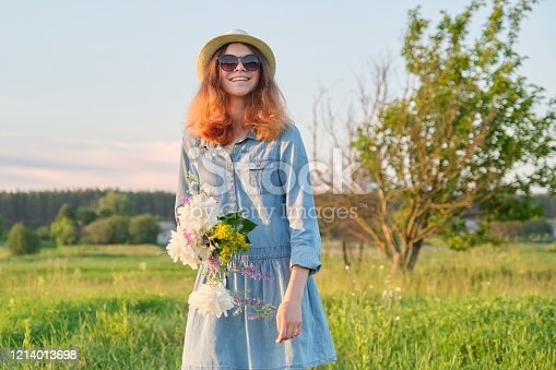 623358818 istock photo Portrait of beautiful teen girl in sunglasses hat with flowers on nature 1214013698