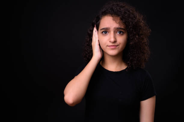 Portrait Of Beautiful Teenager Girl Portrait Of Beautiful Teenager Girl Against Black Background hands covering ears hear no evil teenage girls women stock pictures, royalty-free photos & images