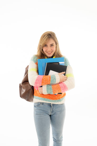 Portrait of beautiful teenager girl with backpack and notepad folder smiling against white background. Young college teen woman happy to start university. in People Education and student lifestyle. stock photo
