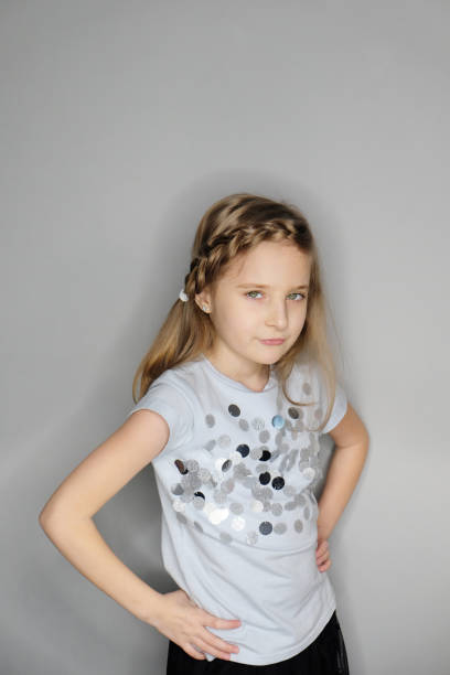 Portrait of beautiful unpleased posing little girl with attentive look stock photo