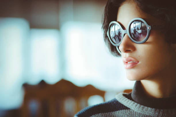 Portrait of beautiful urban young woman. Indoor image of beautiful serene Asian young woman sitting in restaurant and looking at view. She is wearing black round sunglasses. One person, headshot and selective focus with copy space. asian woman wearing shades stock pictures, royalty-free photos & images